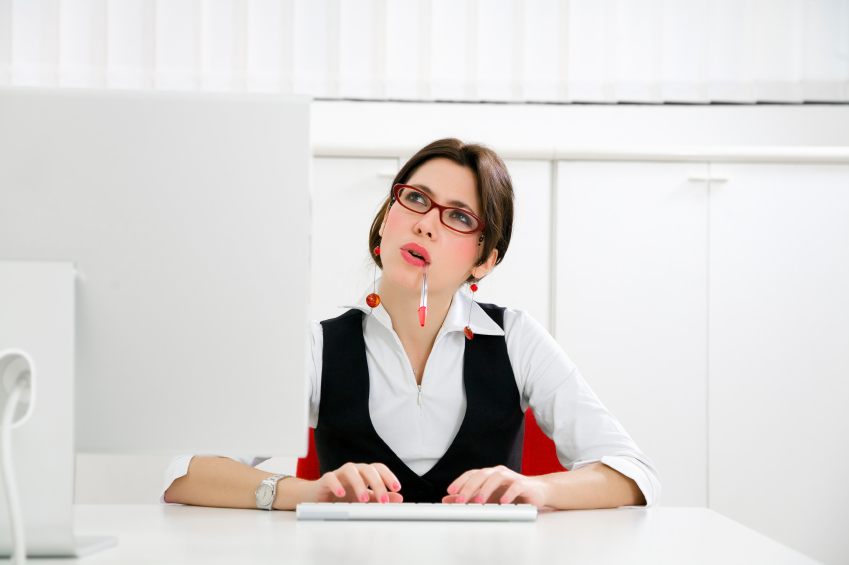 Young businesswoman in office typing on computer
